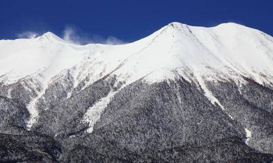 雪煙舞う御岳摩利支天と飛騨頂上