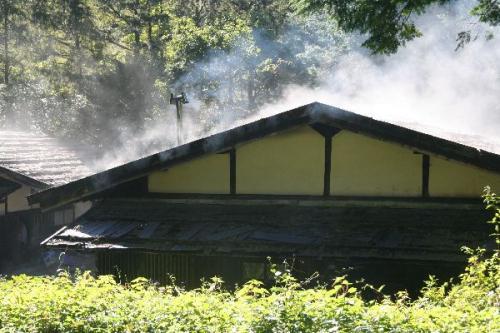 蒸気を上げる板葺屋根