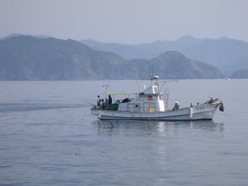 磯の前で釣る船